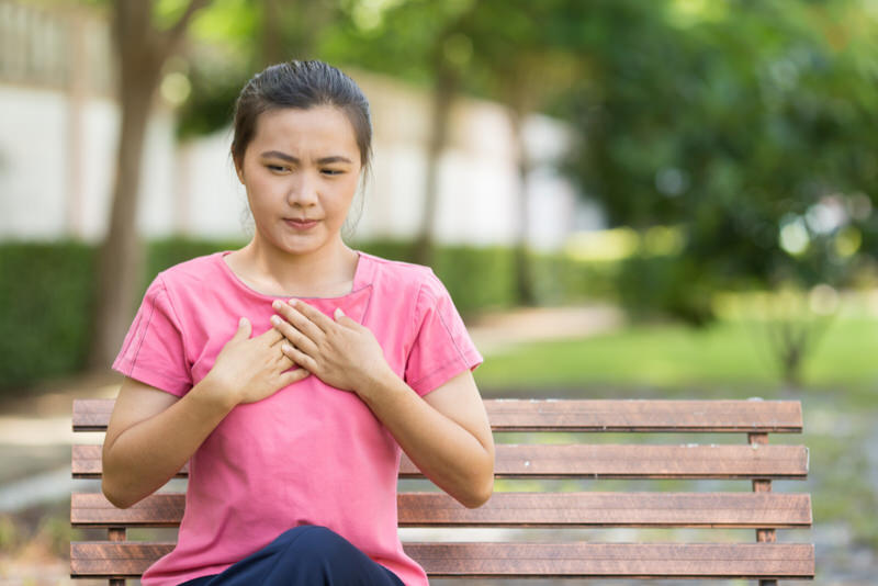 A young woman sat down on a bench at the park after feeling acid reflux like symptoms.