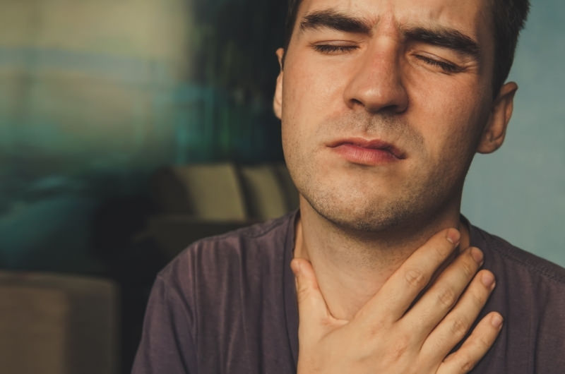 A young man is clenching his throat after feeling sharp pain by his Adam's Apple.