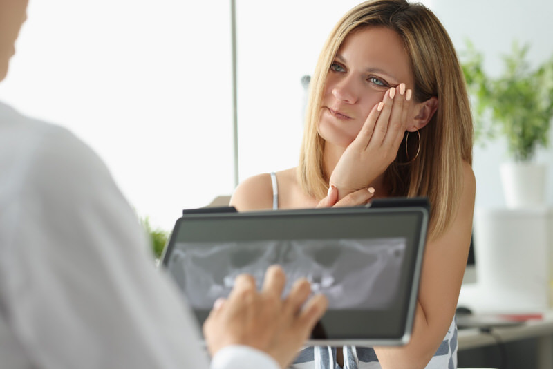 A woman is having a followup meeting with her oral surgeon a few days after her tooth extraction.