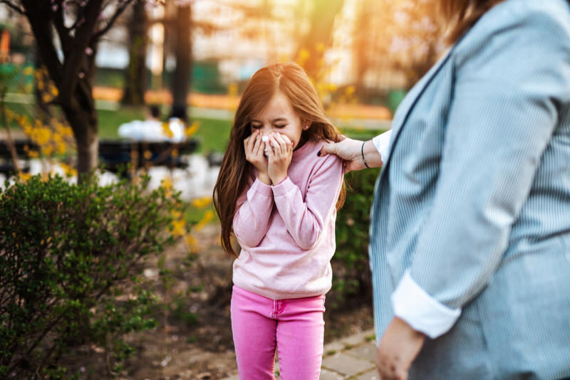 A little girl stopped walking at the park to blow her nose, which feels stuffy and blocked.