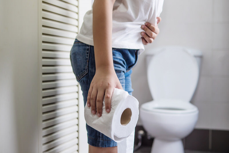 A young man is clenching the right side of his stomach and is heading to the bathroom with a toilet paper roll.