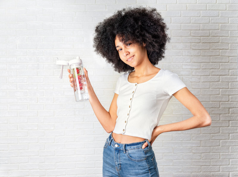 A young girl is drinking fruit-infused water to help ease her nausea everything she drinks water.