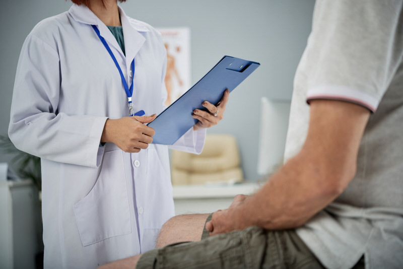 A doctor is recommending his patient to use a heating pad for relief from his after-surgery pain.