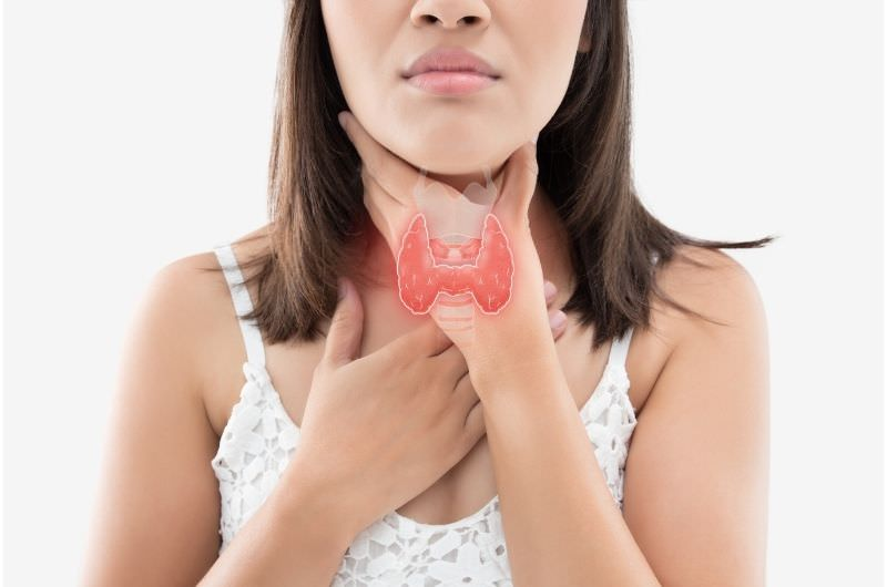 A young woman is clenching her throat in pain after eating. She's been feeling cold every time after she eats.