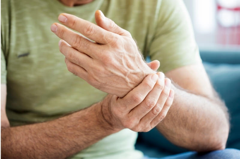 A man is holding his left hand because he's feeling throbbing pain after trying to lift something.