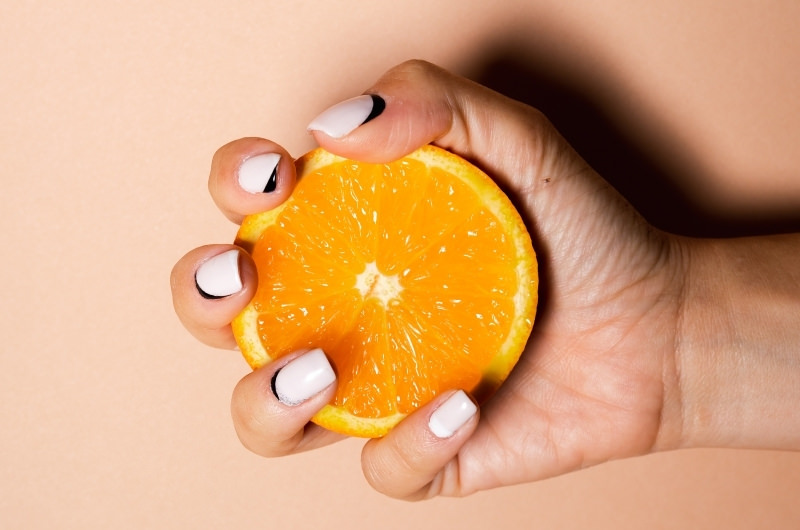 A woman is holding half of a navel orange, on that usually doesn't have any seeds.