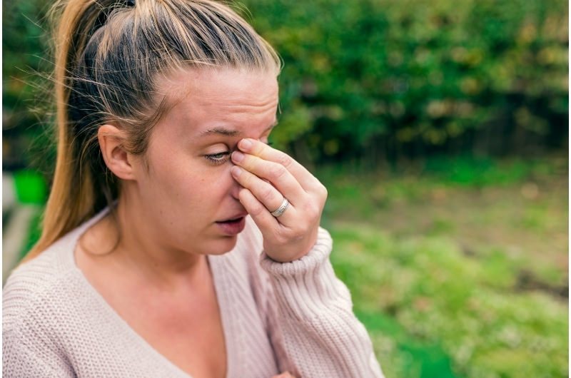 A woman is clenching the sides of her nose because she's having a headache along with sinus conditions.