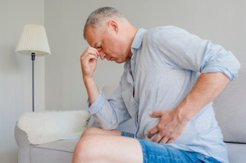 A man is sitting on the sofa clenching his stomach, which is in pain and feels as if someone punched him in the stomach.