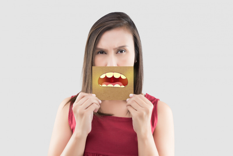 A woman is hiding her mouth behind a postcard because of bad breath, which she thinks might be caused by her Adderall medication.