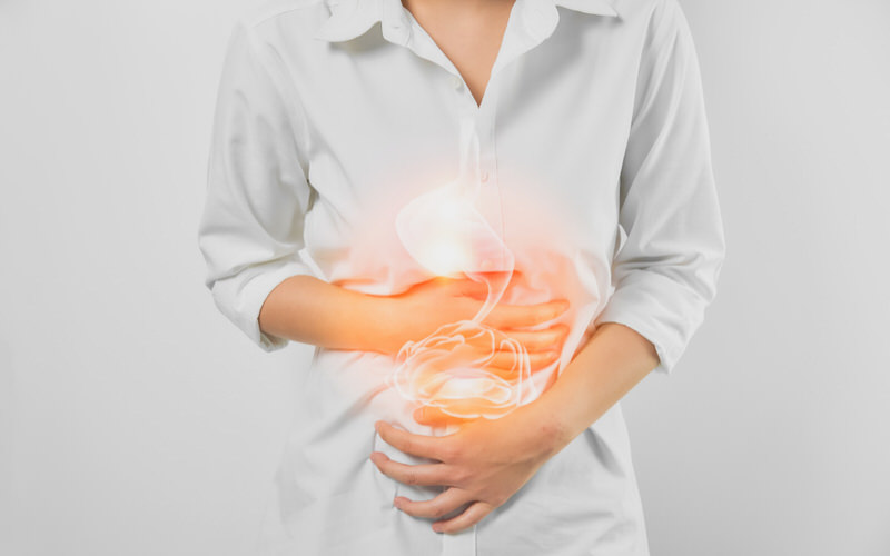 A woman is having a painful sensation in her stomach and is clenching her lower abdomen area.