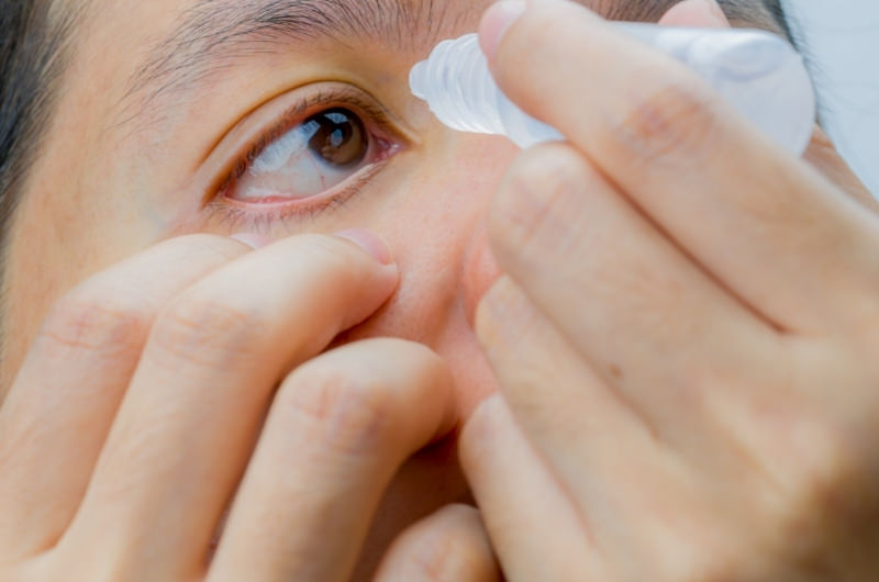 A young man is using eye drops to help clear his eyes from some toothpaste that accidentally got in.