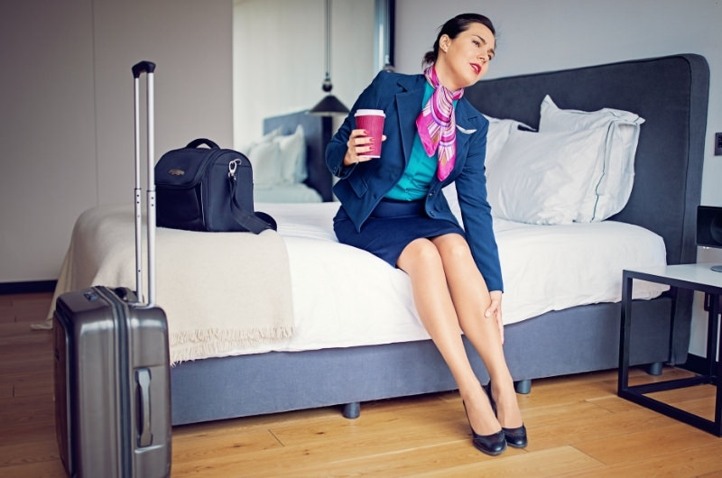 An air hostess is in her hotel room after work and is experiencing ankle swelling pain after being in the airplane.