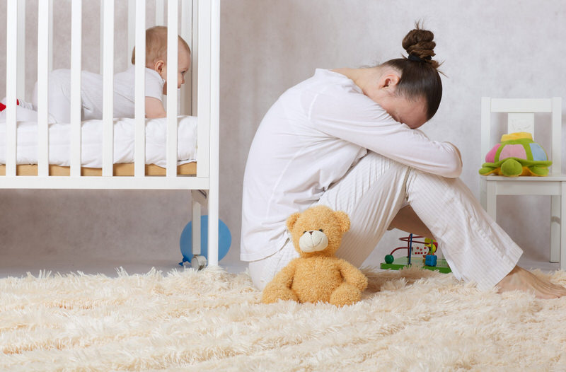A new mom who's experiencing postpartum depression is sitting next to her baby's crib tired and unhappy.