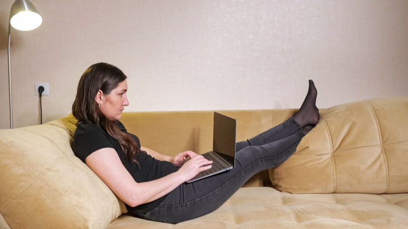 A woman who's traveling is working in her hotel room with her legs raised, to allow her ankles swelling to go down.