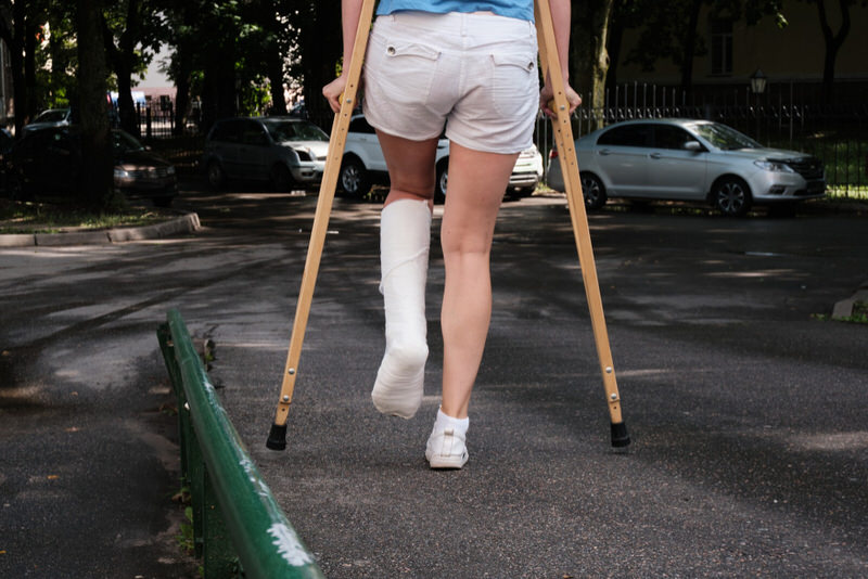 A woman who has a cast on her left foot is using crutches to get to her car after visiting her doctor for a checkup on her injury.