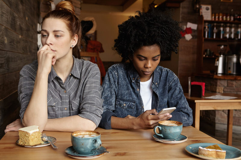 A young woman is at a coffee shop with her friend, but is not conversing with her friend, she has a hard time making small talk.
