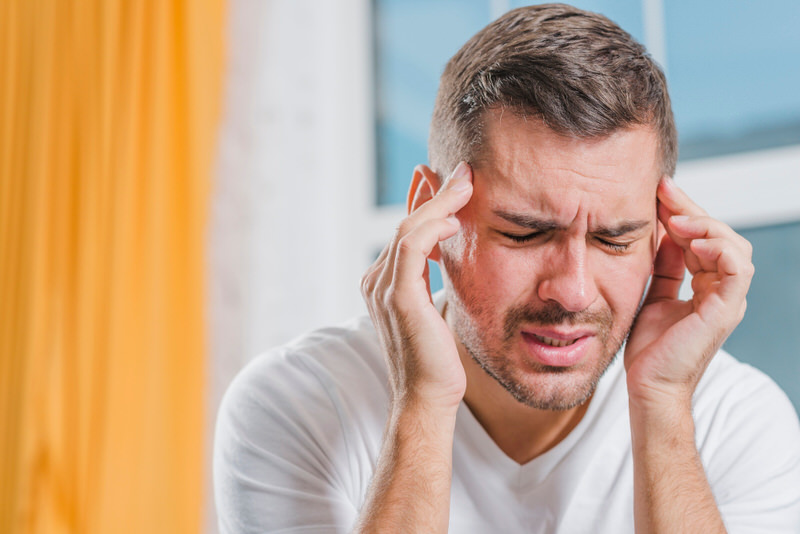 A man is touching his head as he's having a severe headache, a symptom of Cerebrospinal Fluid Leak.