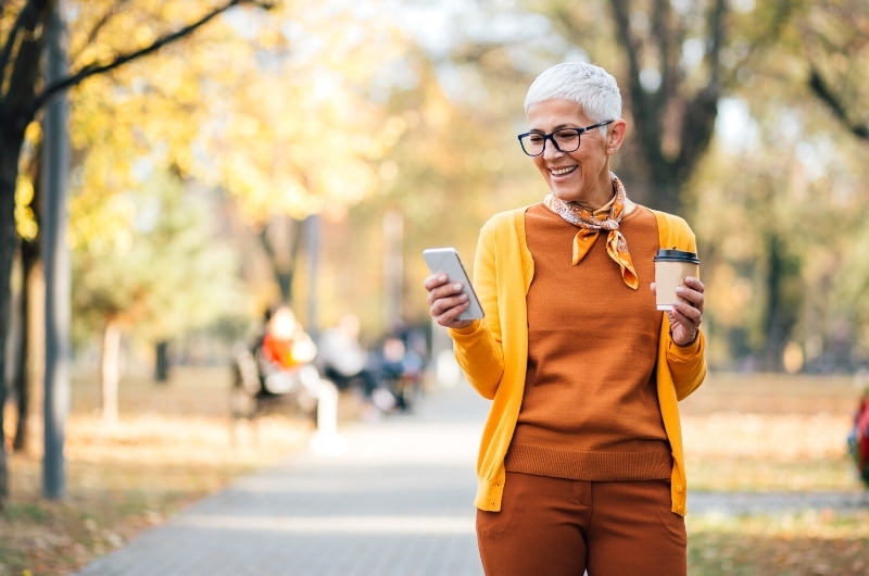 An older woman is holding coffee and walking in the nearby park to avoid sitting for too long and prevent varicose veins.