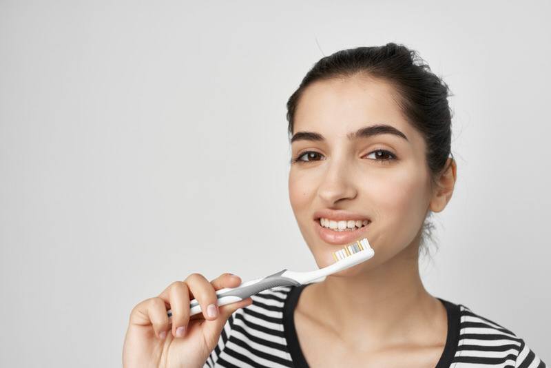 A young woman is about to start brushing her teeth.