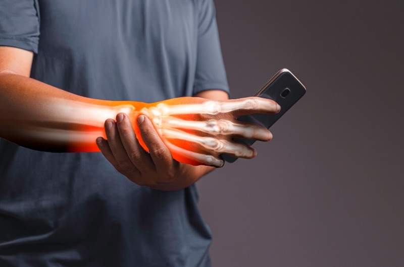 A graphic showing a man holding his phone but experiencing pain in his palm as a result of having carpal tunnel syndrome.