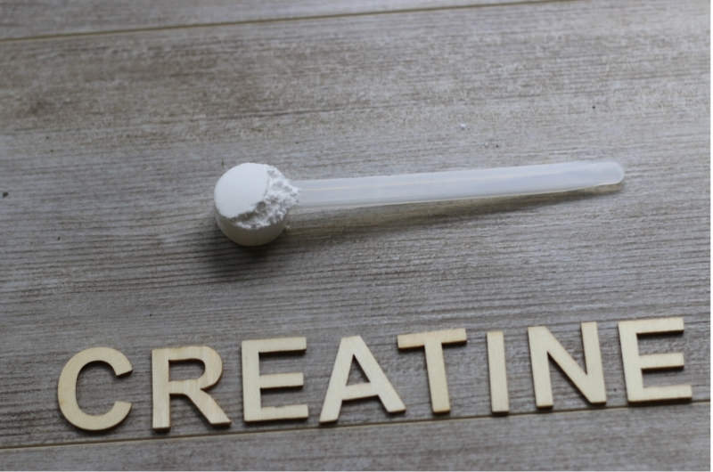 A scoop of creatine is shown next to the spelled out wording for creatine.