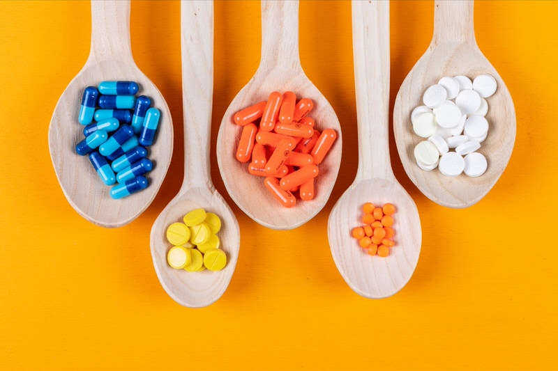 A variety of different types of pills are laid out on different wooden spoons to show their differences .