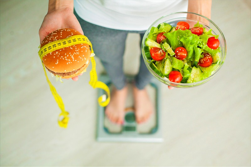 A woman is standing on a scale while holding a salad in one hand and a burger in another. She's struggling to balance her weight loss goals with her food cravings.