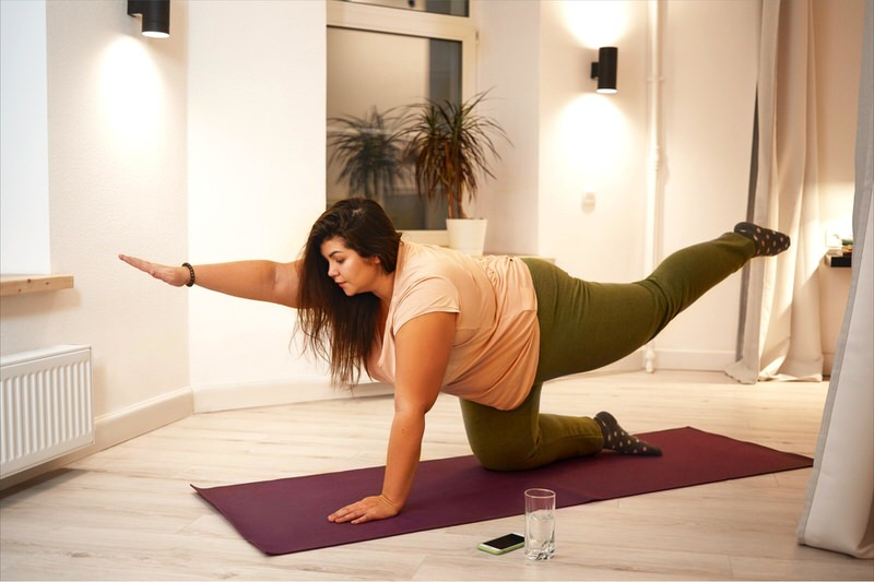 A young woman is doing yoga to start her journey towards weight loss.