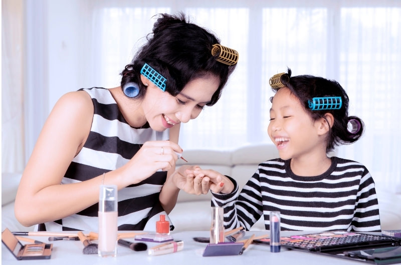 A mom and daughter are happily painting their nails together at home.