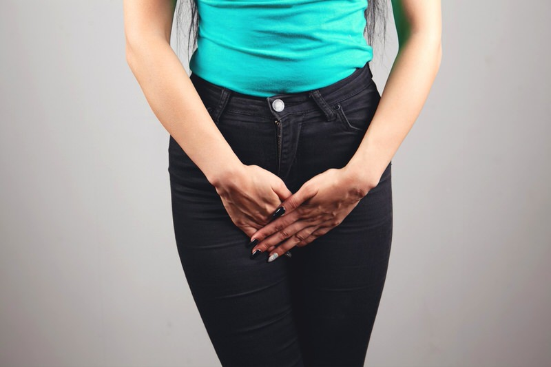 A woman is shown putting her hands over her bladder, she's had to use the bathroom frequently after having hip replacement surgery.