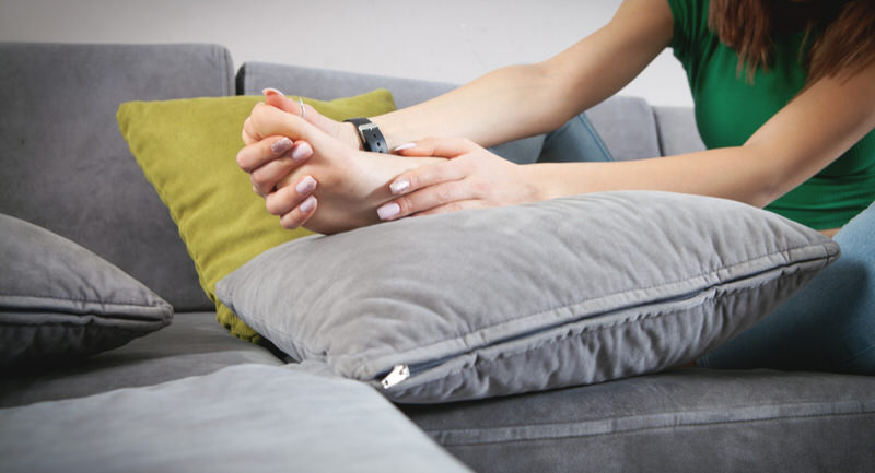A young woman is on the sofa massaging her painful pinky toe.
